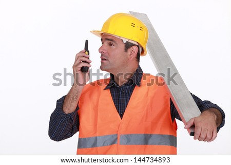 Labourer speaking into a walkie-talkie - stock photo