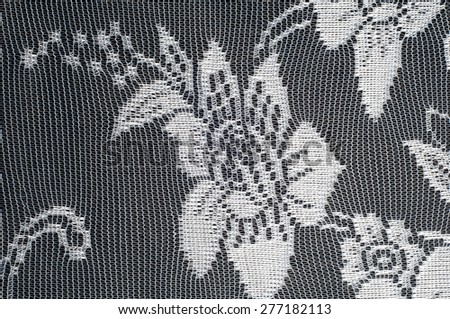 Lace on black and white fabric. a fine open fabric, typically one of cotton or silk, made by looping, twisting, or knitting thread in patterns and used especially for trimming garments. - stock photo