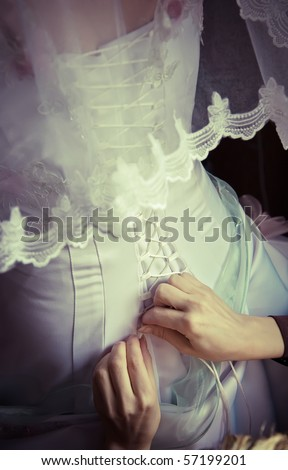 Lacing up the wedding dress - stock photo
