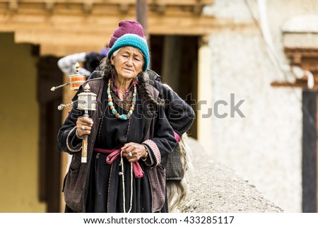 LADAKH, INDIA - 2016 MAY 14 : An unidentified tibetan Buddhist devotee holding prayer beads and wheel. - stock photo