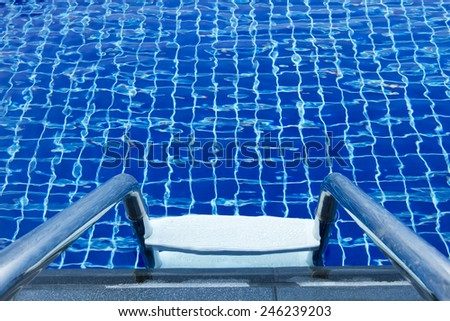 Ladder of a swimming pool with blue water and refreshing. For background - stock photo