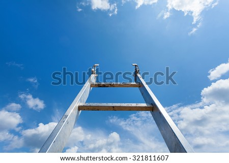 Ladder reaching into a blue sky and clouds - stock photo