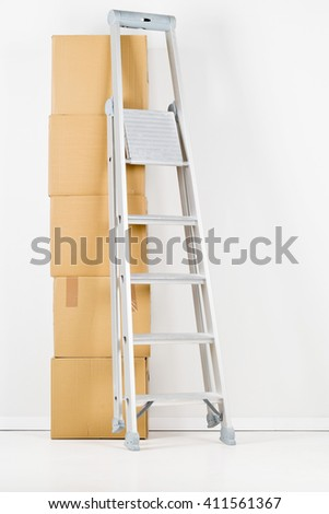 Ladder with stack of moving carton boxes in front of white wall - stock photo