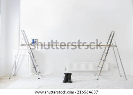 Ladders, wood plank, paint can and work boots in living room - stock photo