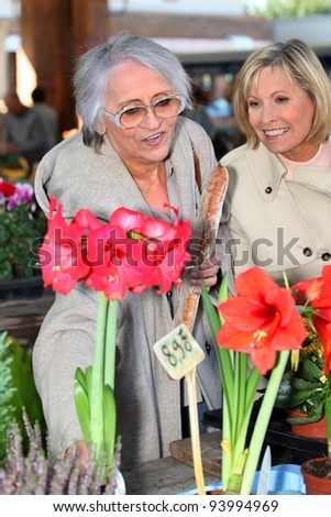 ladies contemplating flowers - stock photo