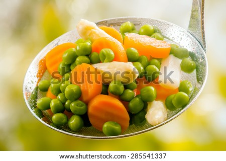 Ladle of steamed freshly harvested young vegetables including crinkle cut sliced carrots, peas and potato batons for a healthy accompaniment to dinner - stock photo