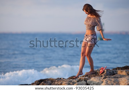 Lady at the sea. Attractive young woman in shorts and blouse on background of sea. Barefoot girl walking along the rocky beach - stock photo