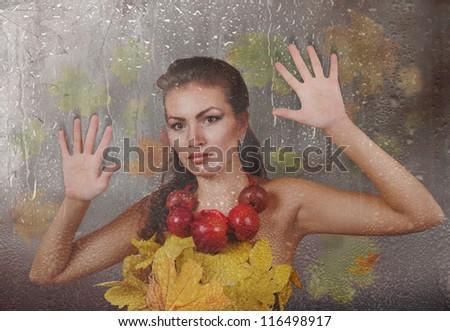 Lady Autumn looking through wet rainy window - stock photo