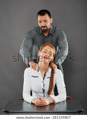Lady boss getting a massage from her handsome employee - stock photo