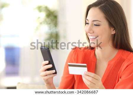 Lady buying online with a credit card and smart phone sitting on a couch at home with a blurred background - stock photo