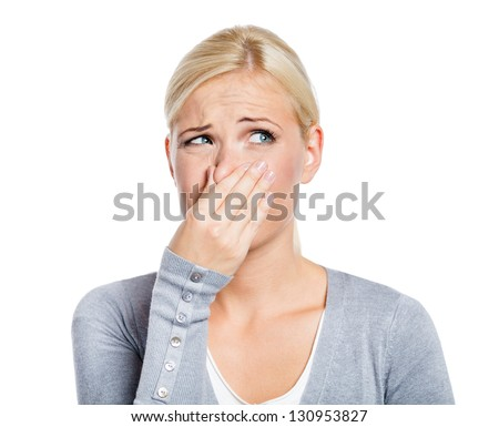 Lady covers nose with hand showing that something stinks, isolated on white - stock photo