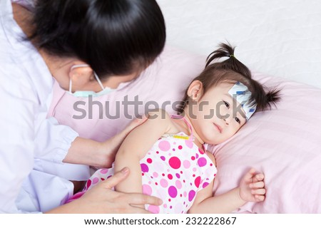 Lady doctor touching arm little asian girl,girl lying on sickbed - stock photo