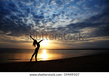Lady doing exercise at the beach during sunset. Vivid colors and natural darkness - stock photo