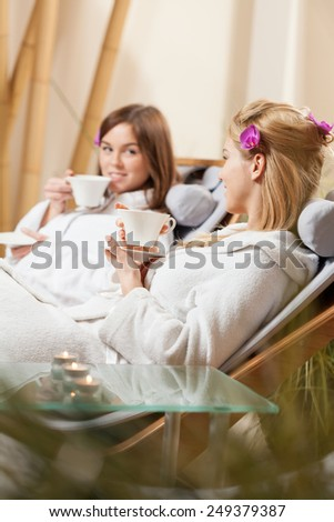 Lady friends drinking tea at spa room - stock photo