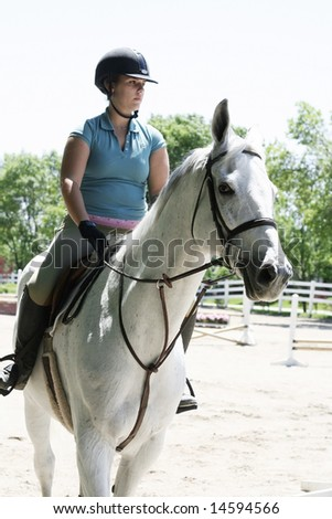 Lady getting horse ready to jump hurdles - stock photo