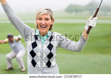 Lady golfer cheering at camera with partner behind on a foggy day at the golf course - stock photo