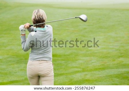 Lady golfer teeing off for the day on a foggy day at the golf course - stock photo