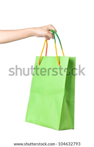 Lady hand holding green paper shopping  bag with  beautiful  color rope handle on white background - stock photo