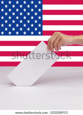 Lady hand putting a voting ballot in slot of white box isolate and flag of USA - stock photo
