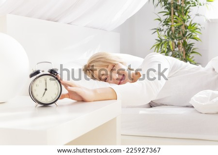 lady has woken up by an alarm clock. eyes closed - stock photo