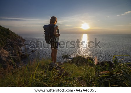 Lady hiker standing on the rock and enjoying sunset over sea - stock photo