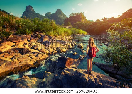 Lady hiker standing on the rock and enjoying view of the river - stock photo