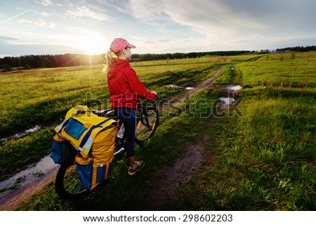 Lady hiker standing on the rural wet messy road with loaded bicycle - stock photo