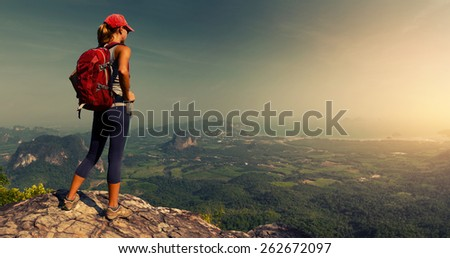 Lady hiker with backpack standing on top of the mountain and enjoying valley view - stock photo