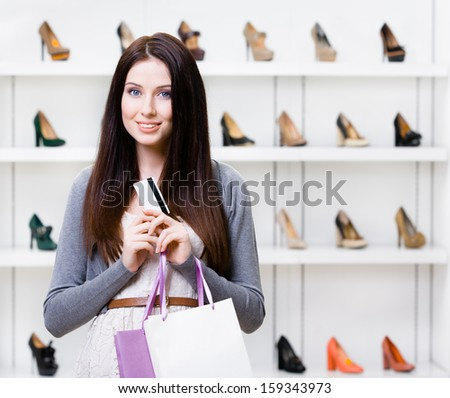 Lady holds credit card in footwear shop with great variety of stylish shoes - stock photo