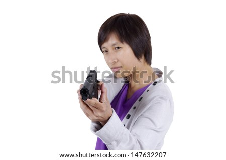 Lady in action pose as she aims a weapon through front.  - stock photo