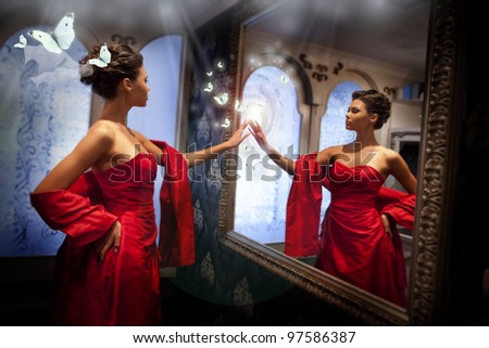 Lady in red and magic mirror - stock photo