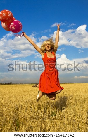 lady in red jumping with balloons - stock photo