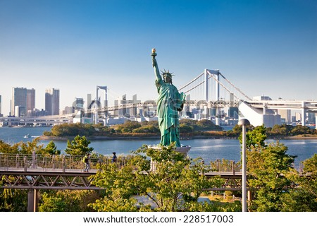 Lady liberty juxtaposed against Rainbow Bridge in Tokyo, Japan. - stock photo