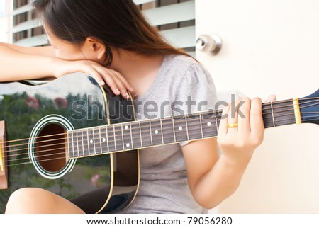 Lady not playing classic acoustic guitar. - stock photo