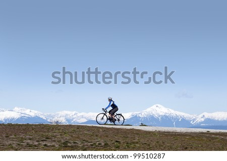 Lady on the bike with mountains in the background - stock photo