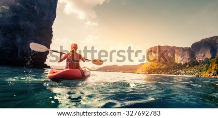 Lady paddling the kayak in the calm tropical bay at sunset - stock photo