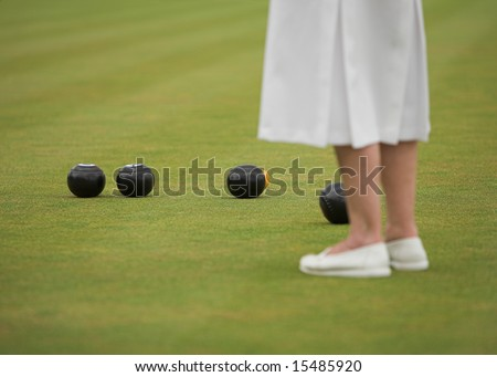Lady player in a game of lawn bowls. - stock photo