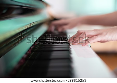 Lady playing piano with selective focus and shallow depth of field. - stock photo