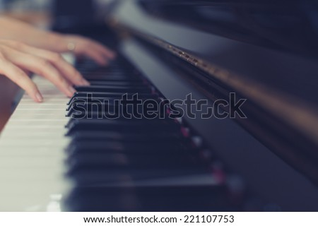 Lady playing piano with vintage look - stock photo