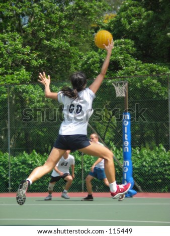 Lady reaching for a Netball - stock photo