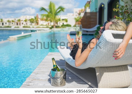 Lady relaxing in deck chair by the pool and drinking champagne - stock photo