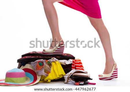Lady's leg on filled suitcase. Legs in striped wedge shoes. Things are finally packed. Long journey requires preparation. - stock photo