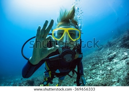 Lady scuba diver showing ok signal underwater - stock photo
