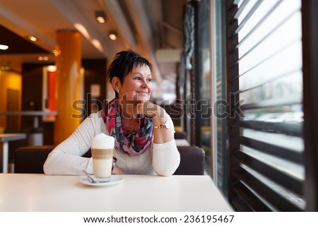 Lady sitting alone drinking coffe and looking through a window. - stock photo
