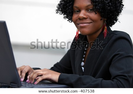 Lady smiles as see types on the computer - stock photo