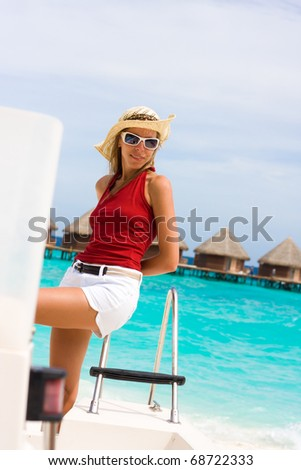 Lady stands abovedeck white yacht at a tropical coast - stock photo