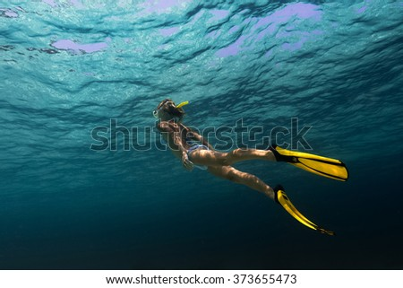 Lady swimming underwater in a tropical sea - stock photo