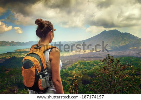 Lady tourist with a backpack standing on top of the mountain and enjoy the beautiful volcano Batur. Indonesia - stock photo