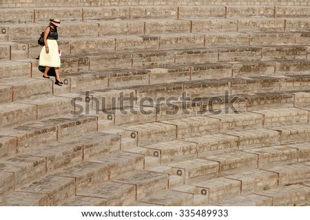 Lady walking down  steps at large theatre in Pompeii, Italy. Pompeii was destroyed and buried with ash and pumice after Vesuvius eruption in 79 AD. - stock photo
