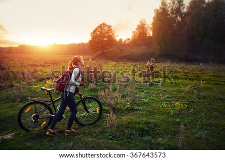Lady walking with bicycle on the green autumn meadow at sunset - stock photo